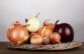 Oignons mûrs sur berceau en osier sur une table en bois sur fond gris — Photo