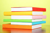 Stack of multicolor books on green background — Stock Photo