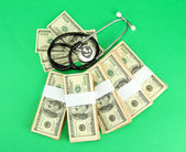 Healthcare cost concept: stethoscope and dollars on green background — Stock Photo