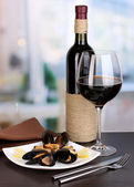 Snack of mussels with lemon and wine on plate on wooden table on room background — Stock Photo