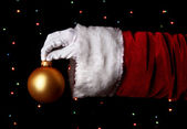 Santa Claus hand holding christmas ball on bright background — Stock Photo