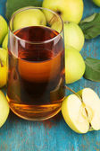Useful apple juice with apples around on wooden table — Stock Photo
