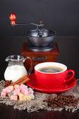 Rojo taza de café con deleite rahat, leche y molino de café en la mesa de madera — Foto de Stock