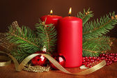 Two candles and christmas decorations, on brown background — Stock fotografie