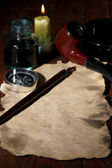 Old paper with ink pen, compass and cigar near lighting candle on wooden table — Stock Photo