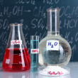 Test-tubes with various acids and other chemicals on the background of the blackboard — Stock Photo