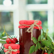 Jars with hip roses jam and ripe berries, on wooden table — Stock Photo #15831835