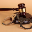 Gavel and handcuffs on beige background — Stock Photo