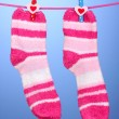 Pair of striped socks hanging to dry over blue background — Stock Photo