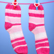 Pair of striped socks hanging to dry over blue background — Stock Photo #15833065
