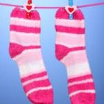 par de listrado meias penduradas para secar sobre fundo azul — Foto Stock #15833065