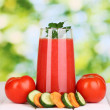 Glass of tomato juice on wooden table, on green background — Stock Photo