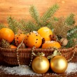 Christmas composition in basket with oranges and fir tree, on wooden background — Stockfoto