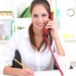 Stock Photo: Young pretty business woman with phone writing at office