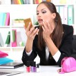 Young business woman looking in the mirror and putting some makeup by office work - Stock Photo