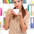 Young businesswoman drinking coffee - Stock Photo