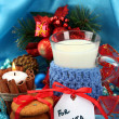 Cookies for Santa: Conceptual image of ginger cookies, milk and christmas decoration on blue background — Stock Photo #15835297