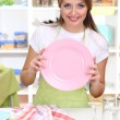 A young girl dries dishes in kitchen — Stock Photo #15835579