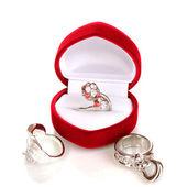 Bague en argent avec cristaux rouges, roses et clairs dans la boîte de velours rouge et quelques anneaux d'argent isolé sur blanc — Photo