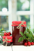 Jars with hip roses jam and ripe berries, on wooden table — Stock Photo