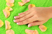Woman's hand on green terry towel, close-up — Stock Photo