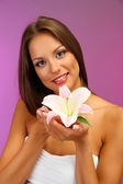 Beautiful young woman with lily, on purple background — Stock Photo