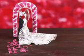 Decorativo casado, amando o casal na mesa de madeira em fundo vermelho — Foto Stock
