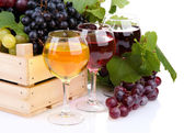 Glasses of wine and assortment of grapes in wooden crate, isolated on white — Stock Photo