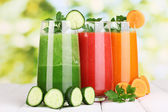 Fresh vegetable juices on wooden table, on green background — Stock Photo