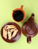 Top view of cup of tea and teapot on green tablecloths — Стоковое фото