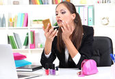 Young business woman looking in the mirror and putting some makeup by office work — Stock Photo