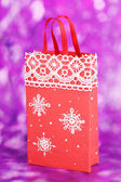 Christmas paper bag for gifts on purple background — Stock Photo