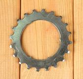 Roda dentada de metal no fundo de madeira — Fotografia Stock