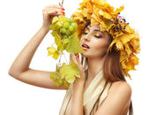Beautiful young woman with yellow autumn wreath and grapes, isolated on white — Stock Photo