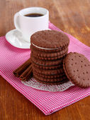 Chocolate cookies with creamy layer and cup of coffe on wooden table close-up — Stock Photo