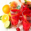 Sangria in jar and glasses with fruits, on white wooden table — Stock Photo