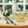 Salad of squid rings, lemon and lettuce in a glass bowl on wooden table close-up — Stock Photo #15842271