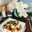 Fresh greek salad on white plate on table on restaurant background — Stock Photo #15843053