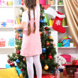Little girl decorates  Christmas tree in festively decorated room — Stock Photo