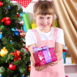 Little girl with Christmas toys in festively decorated room — Stock Photo