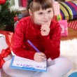 Beautiful little girl in red dress writes letter to Santa Claus in festively decorated room — Stock Photo #15844513