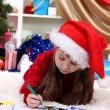 Stock Photo: Beautiful little girl writes letter to SantClaus in festively decorated room