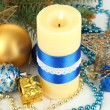 Yellow candle with christmas decoration on light background — Photo