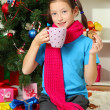 Little girl with pink scarf and cup of hot drink sitting near christmas tree — Stock Photo #15844919