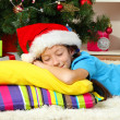 Little girl sleeping near christmas tree — Stock Photo #15844939