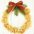 Christmas wreath of dried lemons with fir tree and bow, on white wooden background — Stock fotografie