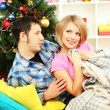 Young happy couple near a Christmas tree at home — Stock Photo #15845519