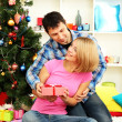 Young happy couple with presents sitting near Christmas tree at home — Stock Photo
