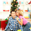 Young happy couple with presents sitting near Christmas tree at home — Stock Photo #15845597
