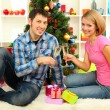 Young happy couple holding glasses with champagne near Christmas tree at home — Stock Photo #15845607